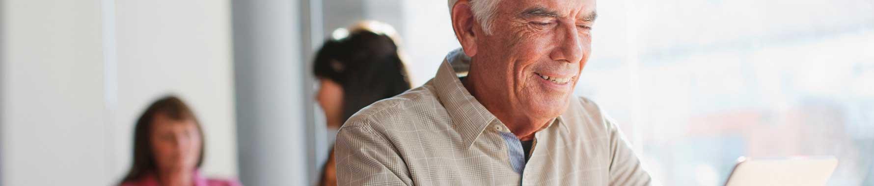 An elderly gentlemen looking at a tablet