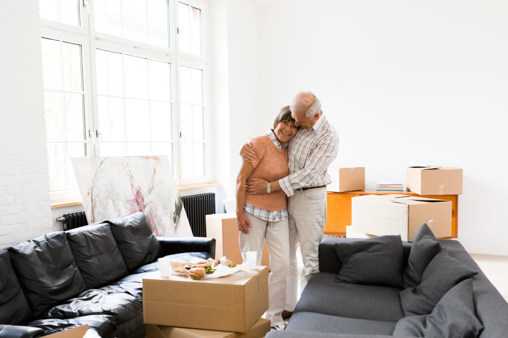 Older couple hugging and smiling in a room with moving boxes.