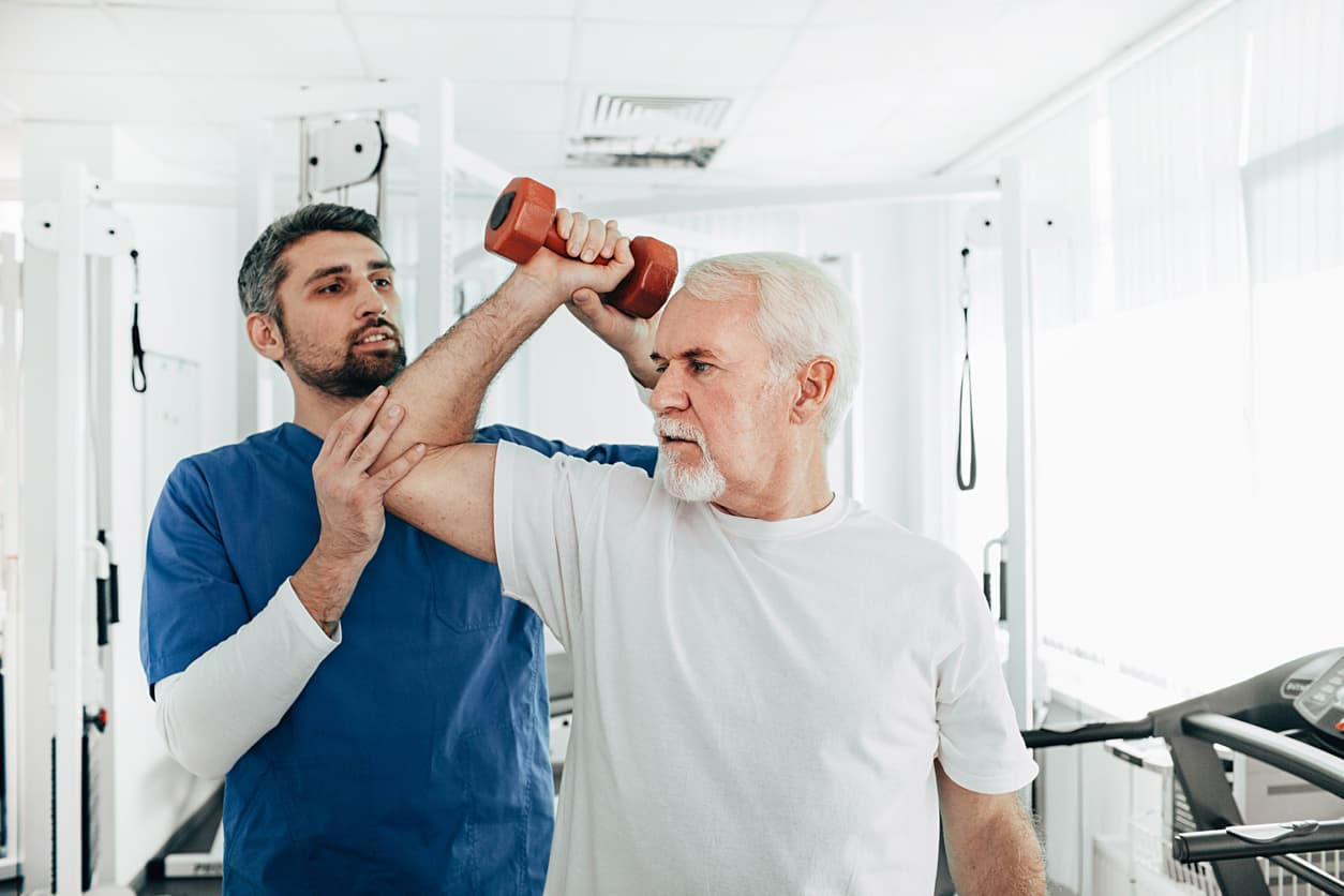 Older man holding a weight with assistance from therapist.