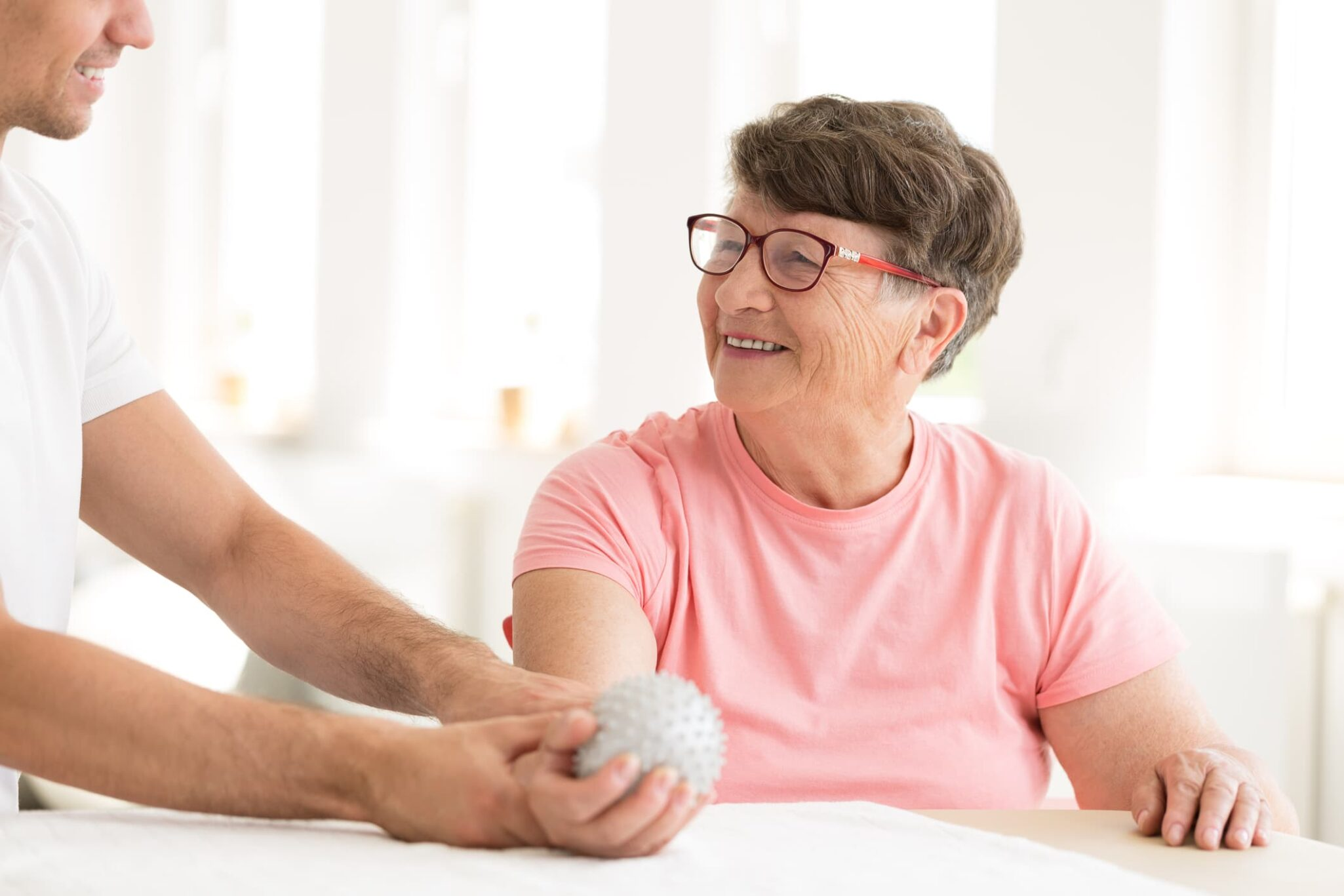 Older woman sitting and smiling at therapist while holding therapy ball in her hand.